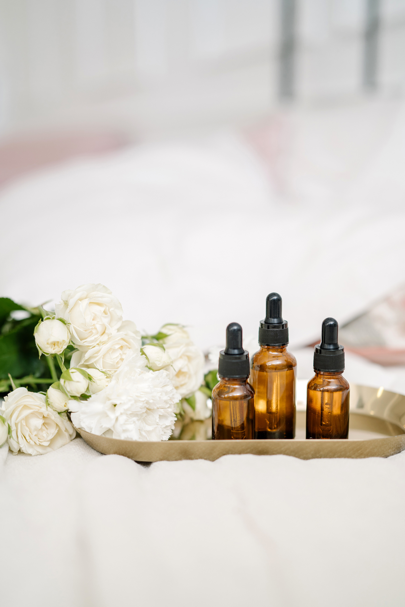 vitamin c serums, beauty tray with white flowers and serum bottles