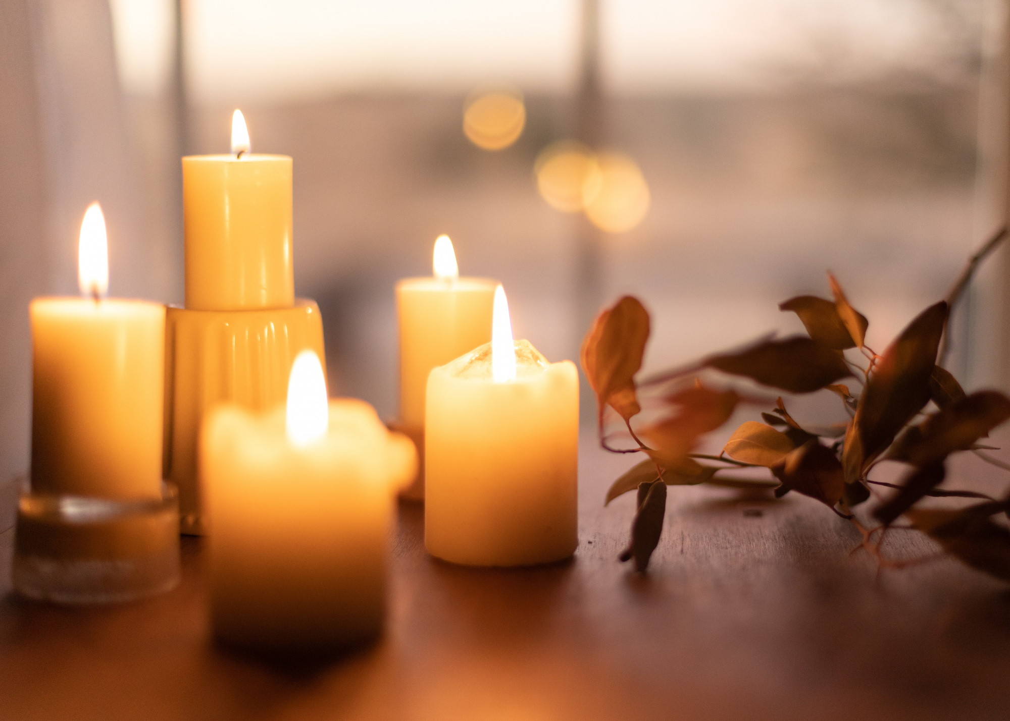 fall-scented candles, home décor with lit candles and leaves on a wooden table