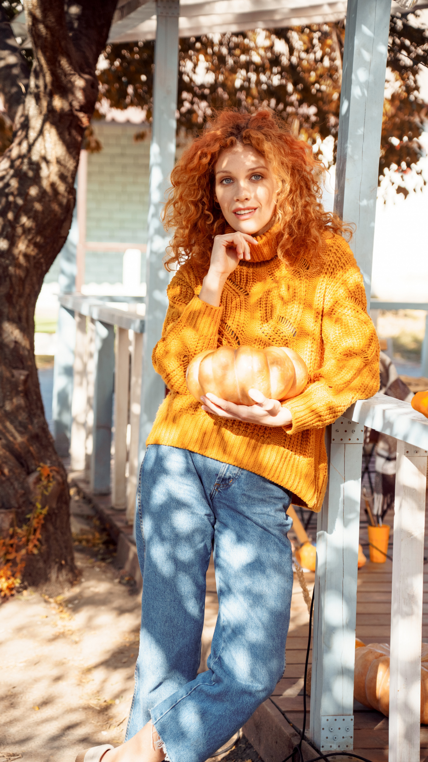 autumn self-care products, Red-haired woman in gold sweater and jeans holding pumpkin